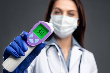 Female doctor in medical mask with infrared thermometer