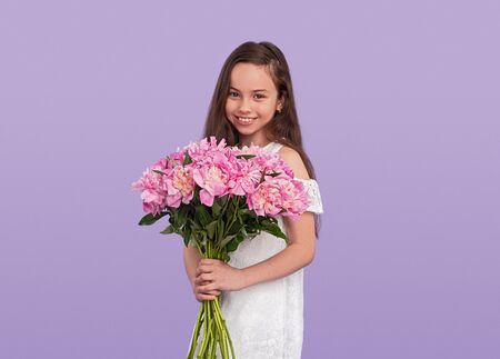 Happy teenager in wig carrying flowers 스톡 콘텐츠