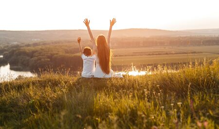 Anonymous brother and sister enjoying sunset in countryside Banco de Imagens