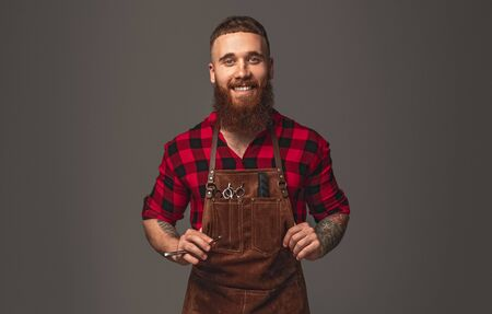 Serious bearded stylish adjusting apron