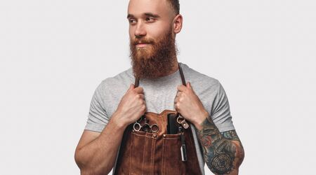 Stylish barber in apron looking away Banco de Imagens