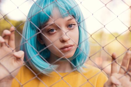 Teen girl in blue wig behind net fence