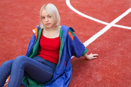 Teen hipster sitting on sports ground Banco de Imagens