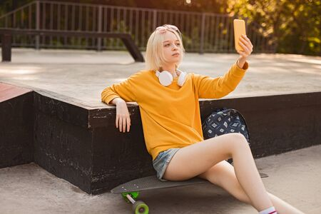 Teen skater taking selfie near ramp
