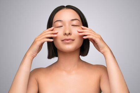 Asian woman touching cheeks under closed eyes