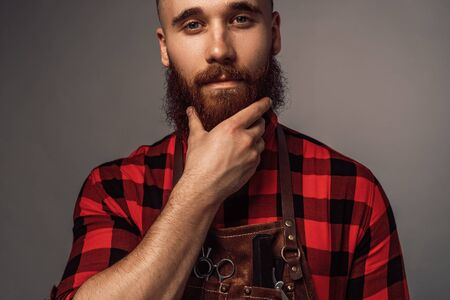 Crop stylish hairdresser stroking beard Banco de Imagens