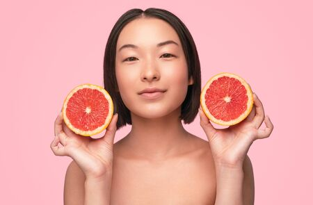 Asian female model with citrus Banco de Imagens