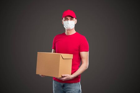 Male courier with protective mask carrying package Banco de Imagens
