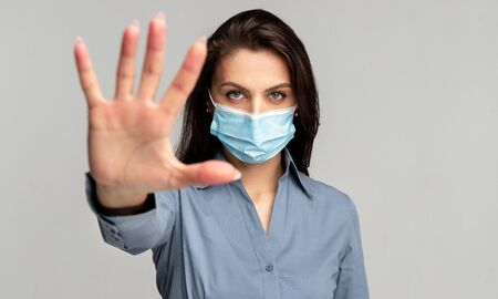 Young woman in protective mask making stop gesture