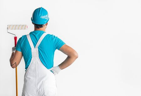 Back view of unrecognizable male painter in blue hardhat and shirt and white overall standing against white wall with paint roller in hand, and preparing for work