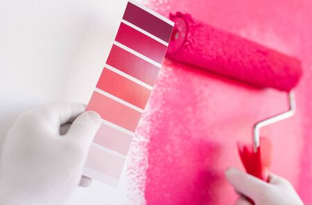 Crop anonymous painter in gloves holding pink color palette and painting wall with roller while working on interior design of modern apartment