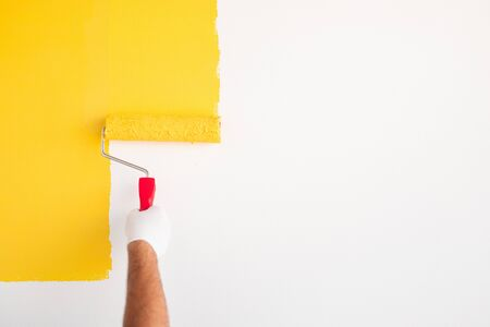 Crop anonymous male worker in protective gloves with paint roller painting wall in bright yellow color while decorating new apartment