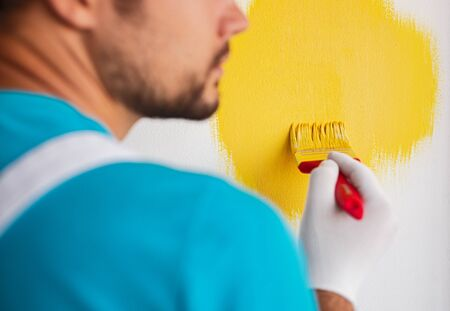 Back view of crop unrecognizable male worker with paintbrush painting wall in bright yellow color while decorating new apartment