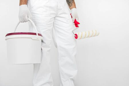 Crop anonymous male worker in white uniform and gloves holding paint roller and plastic bucket with paint while standing against white wall Banco de Imagens