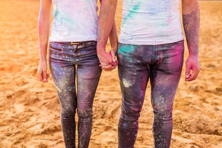 Crop young man and woman with stains of colorful paint on jeans and t shirts holding hands while participating in festival on beach Banco de Imagens