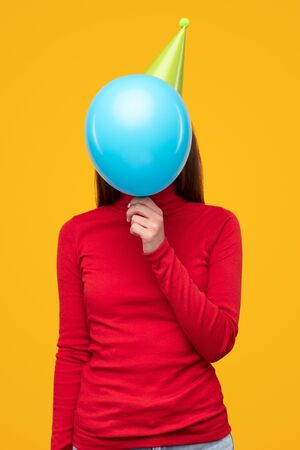 Unrecognizable female hiding face behind blue balloon while celebrating birthday isolated on yellow background