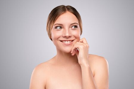Cheerful woman with clean skin looking away
