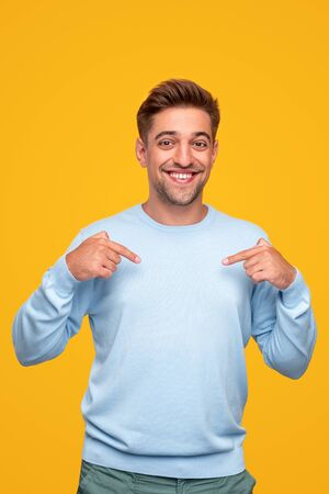 Cheerful man pointing at chest