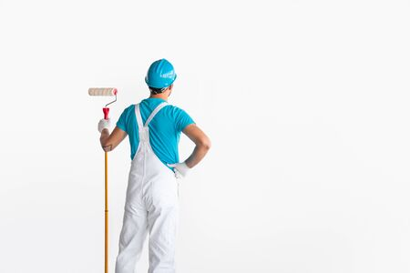 Male worker with painting roller standing against white wall