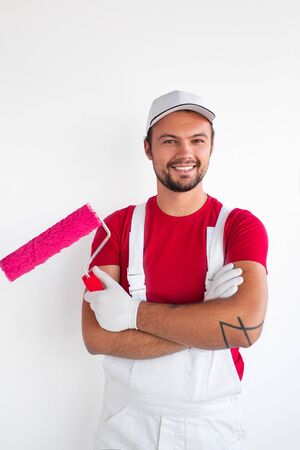 Professional male painter with roller smiling at camera