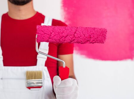 Anonymous worker painting wall in pink color
