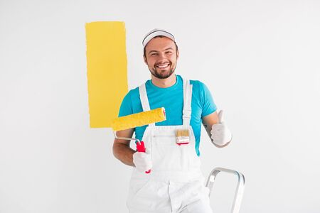 Happy man painting wall and showing approval sign Archivio Fotografico