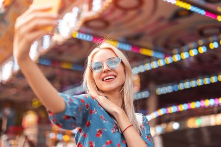 Cheerful young woman taking selfie with smartphone in amusement park 版權商用圖片