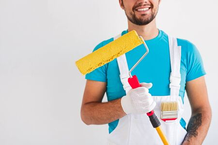 Crop smiling male contractor in blue shirt and white overall with paintbrush and roller standing against white wall during renovation work in modern apartment