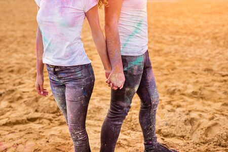 Crop man and woman with colorful paint on casual outfits holding hands and standing on sand during party on beach 版權商用圖片