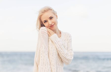 Young blond woman on ocean coast in cool windy day 版權商用圖片