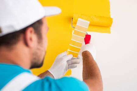Back view of crop professional male decorator holding palette sample and painting wall in bright yellow color while working on decoration of house 版權商用圖片