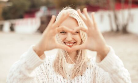 Happy romantic young woman looking at camera and showing heart gesture on street