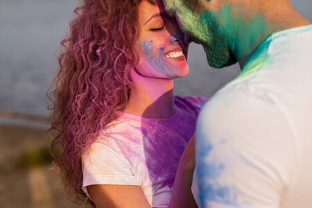 Woman touching noses with boyfriend during paint party