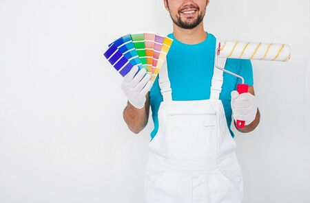 Crop smiling professional male decorator in overall and gloves holding colorful palette samples and paint roller while standing against white wall