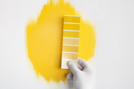 Crop anonymous interior designer holding yellow color palette while choosing paint for decorating of modern room