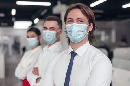 Businessman in medical mask as part of team Imagens