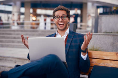 Excited businessman with laptop celebrating success