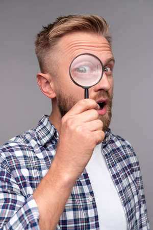 Curious man with magnifying glass looking at camera 版權商用圖片