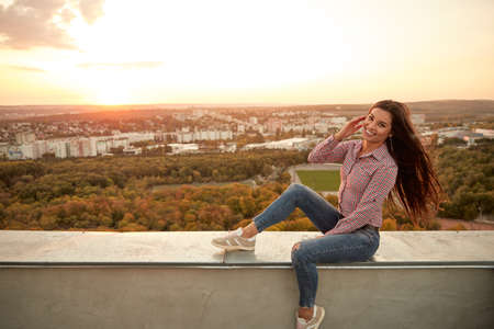 Cheerful woman resting on roof in evening