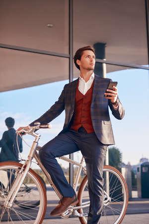 Thoughtful businessman with bike using smartphone on street 写真素材
