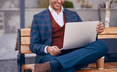 Crop businessman using laptop on bench Foto de archivo