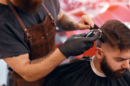 Professional barber trimming hair of bearded man