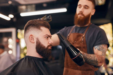 Blurred barber drying hair of client