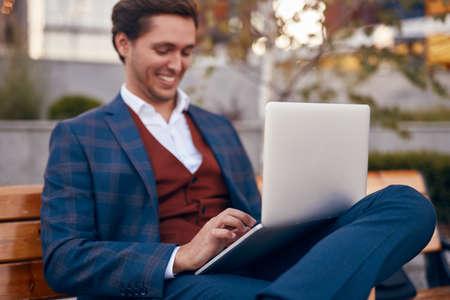 Cheerful businessman using laptop on street
