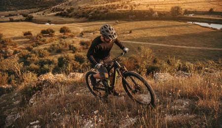 Man with mountain bike climbing hill