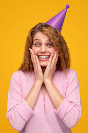 Delighted young woman in party hat