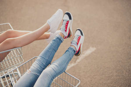 Unrecognizable young women resting in shopping carts