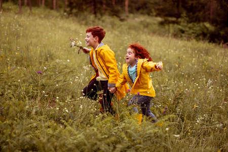 Happy siblings running in grassy meadow