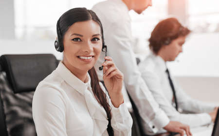 Smiling woman with headset working in customer service center