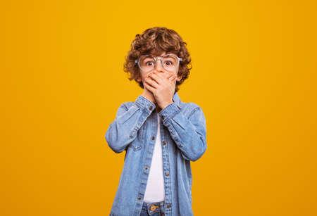 Amazed little boy covering mouth 版權商用圖片